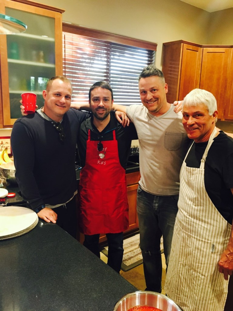 Men smiling together with aprons in the kitchen