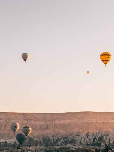 flying air balloons under mountain valley