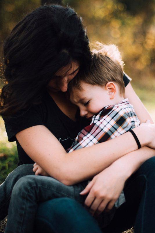 Mamá abrazando a su hijo, visiblemente triste, por no aceptar un destete.