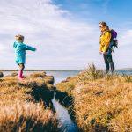Madre e hija separadas por un arroyo, evocando la brecha que ha existido entre maternidad y feminismo