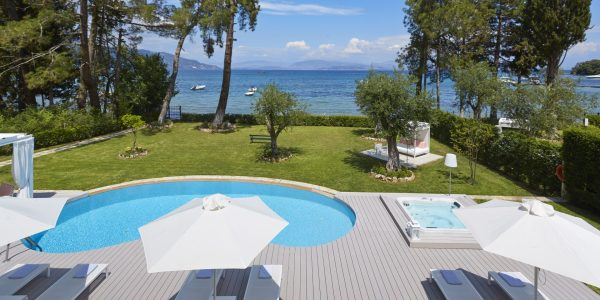 Picture of the outdoor pool, jacuzzi, sunbeds, sun umbrellas and part of the garden with seaviews of the seafront holiday villas Elizabeth and Olive in Corfu, Greece on a sunny day