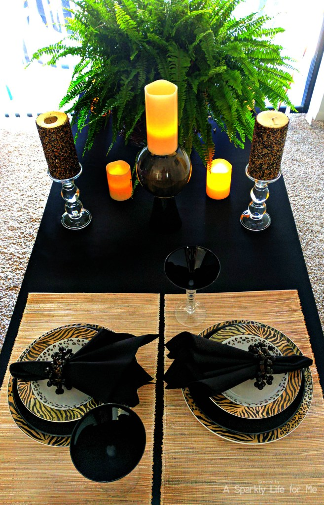 Animal print jungle tablescape with leopard print place setting with black accents and LED candles centerpieces