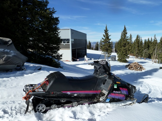 """A snowmobile, with tow ropes for skiers, parked in the """"marina"""" behind the gondola building at the top of Aspen Mtn. The marina, on private land, is to be closed by Aspen Skiing Co, and the sleds may end up on the side of adjacent county roads."""
