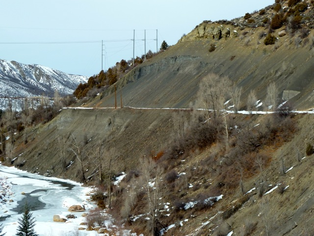 "The ""Shale Bluffs"" section of the Rio Grande Trail. The trail, covered in snow in this photo, has steep and loose slopes both above and below it. A proposed bridge would have crossed the river downstream of the shale cliffs."