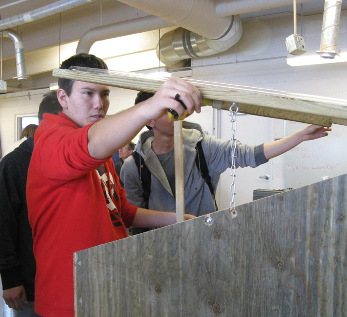 A student in Eric Pedersen's wood shop class measures the cover of a prototype cold frame at Basalt High.