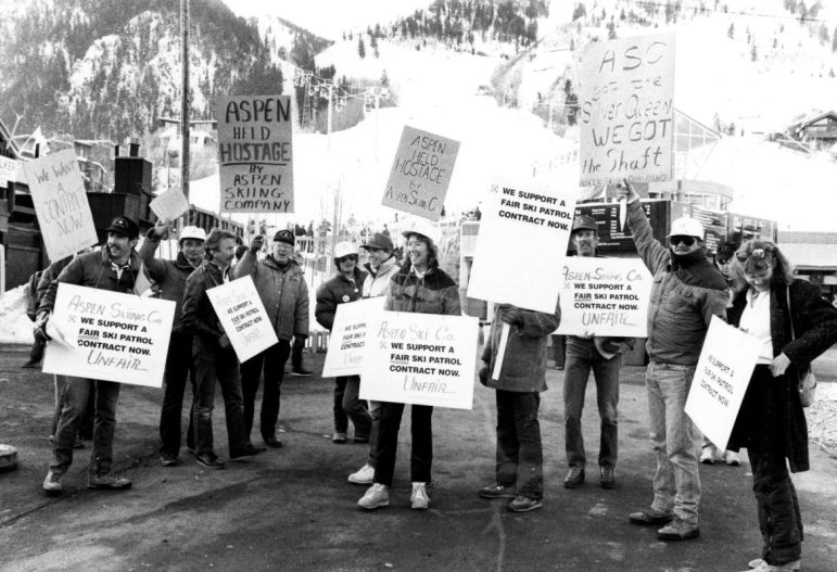 Ski patrollers demonstrating for a fair contract on city property adjoining the gondola plaza during Christmas week, 1986, the year the Silver Queen Gondola opened. While not out on strike, the demonstration was over a yearly termination clause in the contract, which was resolved when support for the ski patrol coalesced throughout town. Ski patrollers on all four ski mountains maintain a union called the Aspen Professional Ski Patrol Association.
