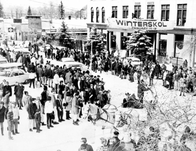 The 1970 Winterskol parade in Aspen. The photo was taken from the corner of Mill and Main, and shows a large crowd watching the parade in front of the Hotel Jerome.