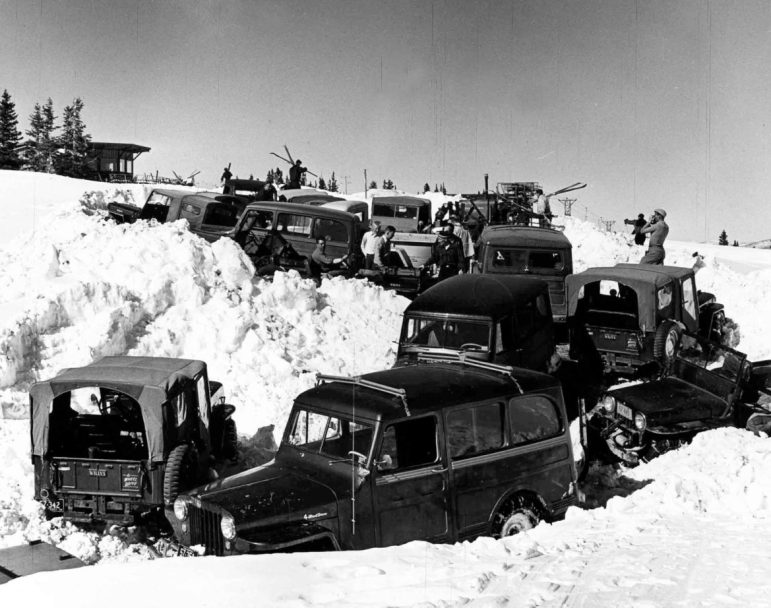Skiers are getting their equipment out of cars after the long ride up from Castle Creek during Operation Jeep Lift in 1954, in an era when everyone in town drove an old jeep. After the Ski Corporation plowed the Little Annie Road, townspeople drove skiers up the backside of Aspen Mountain until repairs on the lift were complete. Sitting in the center jeep is Dave Stapleton. John Thorpe is standing next to him (white shirt, buzz cut) and Neil Beck is standing in front of John (grey shirt), and Euclid Worden in black cap. The original octagon sundeck is on the left. The top of Lift-2 is in the middle background; Lift-3 is on the right.
