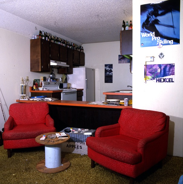 A typical 1975 ski-bum room in the one-time Silver King rental apartments, which are now the condominiumized Hunter Creek buildings. Note the Hexel (revolutionary split-tail ski) ski poster and World Pro Skiing poster, the rustic housekeeping, trophy beer bottles, rolling papers atop the apple box, and the softball trophy on the counter.