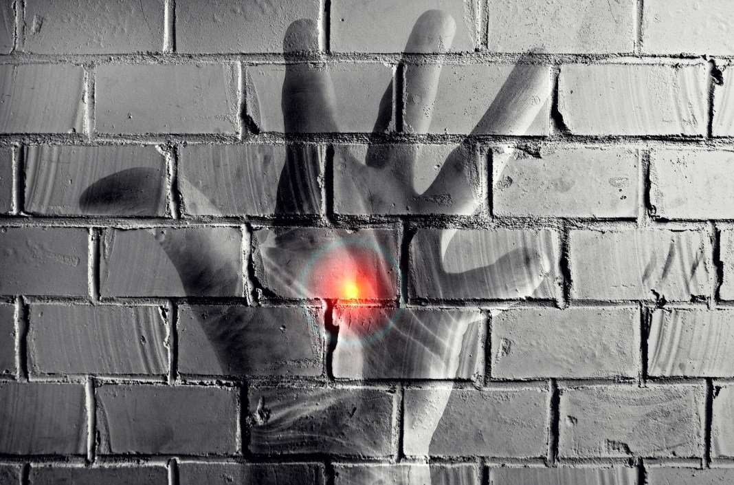 A overlay of a hand and HAL 9000