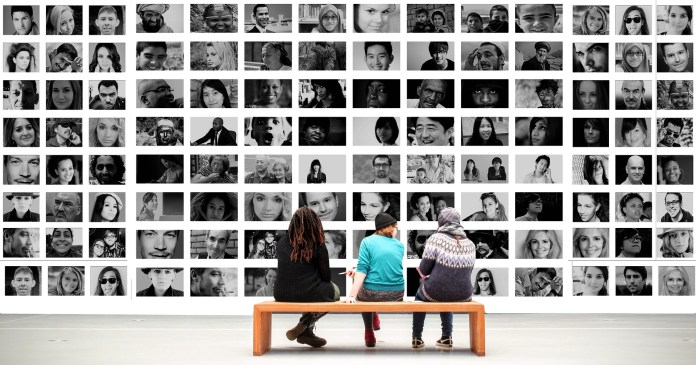 Three people sitting on a bench watching a wall of profiles