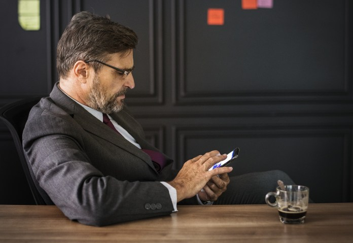 An executive checking his smartphone | Aspioneer