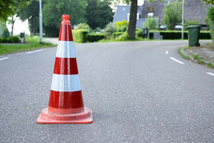 A red white traffic cone on serene empty road | Aspioneer