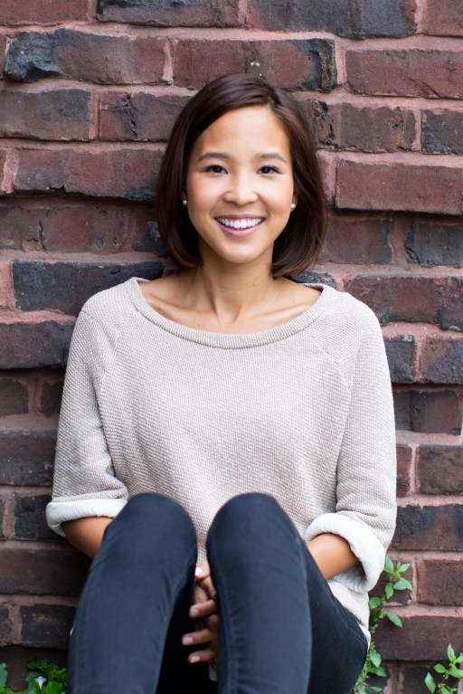 Yunha Kim sitting in front of a brick wall
