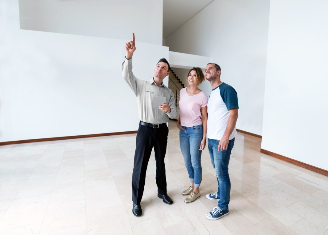 Real estate agent showing a property to a couple and looking very happy
