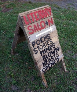 A wooden sign with hand-painted letters: Literary Salo+n, [arrow]. Poems, stories, minds blown, hearts opened