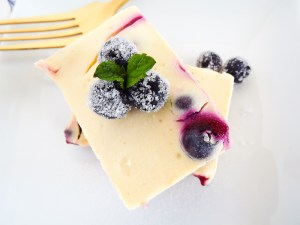 Close up of cheesecake bar on a plate with blueberries on top