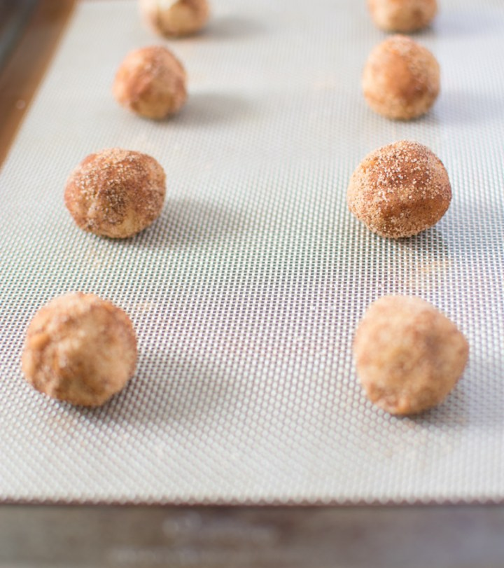 Unbaked cookie dough rolled into balls on a silicone baking mat