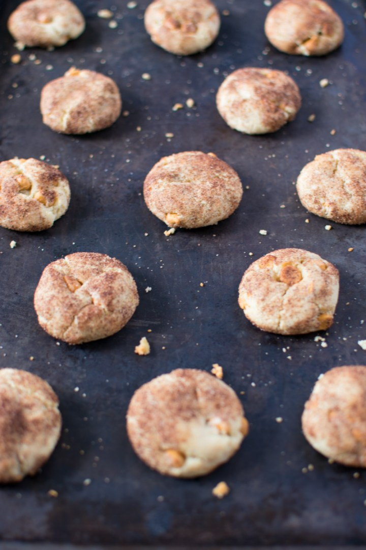 Lots of cookies on a dark baking sheet with cookie crumbs all over