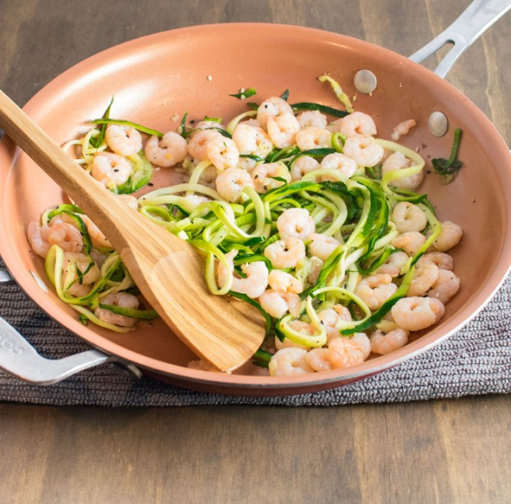 Adding cooked shrimp to zoodles in a skillet