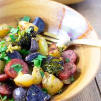 Closeup of smoked sausage and potatoes and veggies in a bowl with a fork