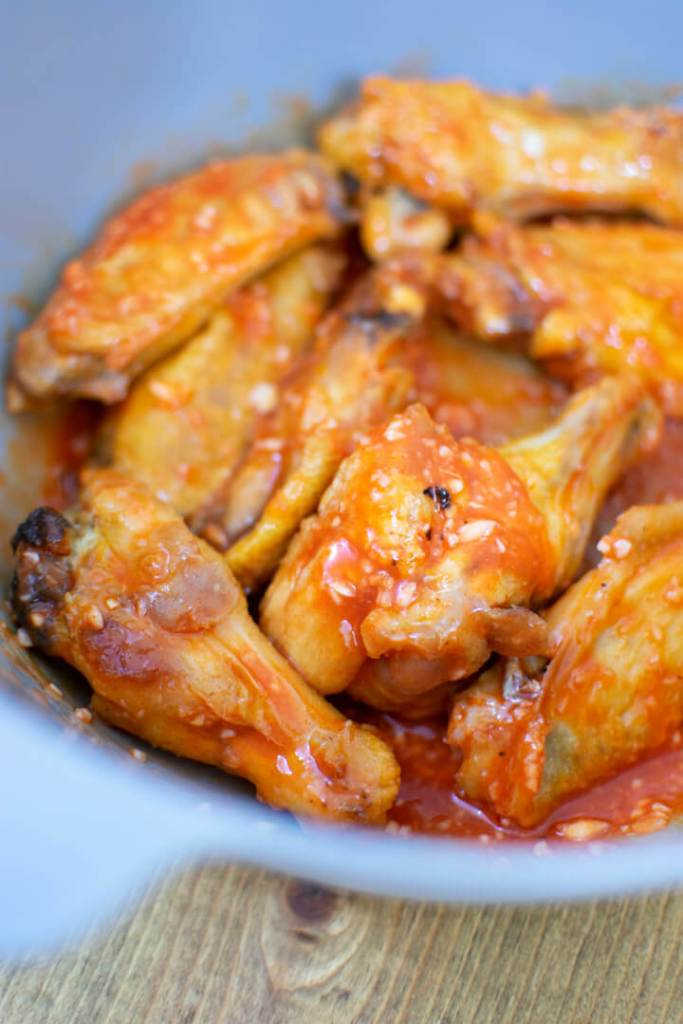 Cooked chicken wings mixed with hot sauce and garlic in bowl