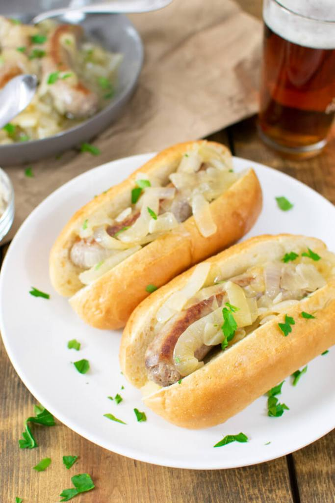 Two butter beer brats in buns on a plate