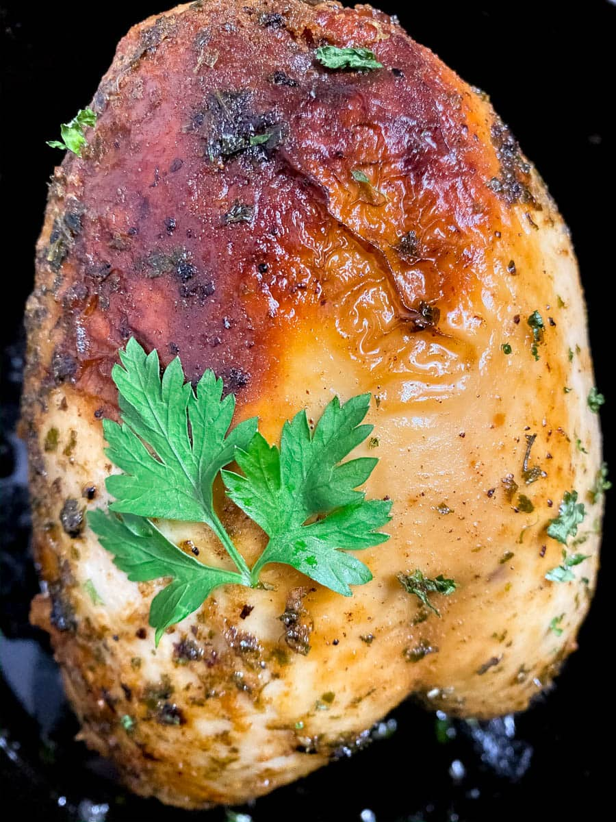 Cajun roast turkey breast in a black cast iron Dutch oven.