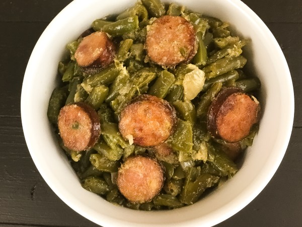Cajun Smothered Green Beans With Sausage in round white bowl against a black background.