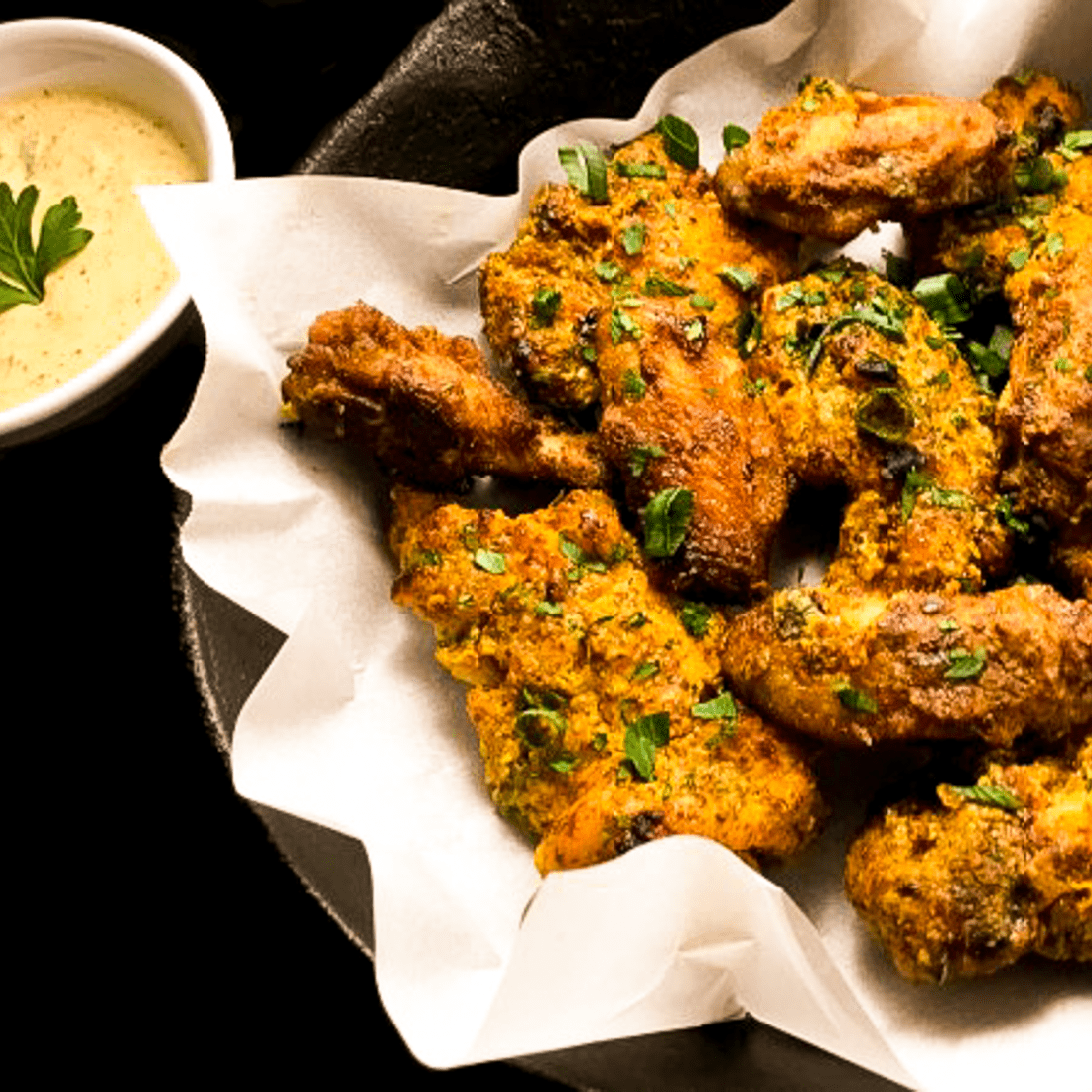 A closeup of gluten free Creole mustard chicken wings and tenders against a black background.
