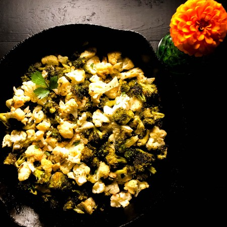 A square shot of Skillet Roasted Broccoli and Cauliflower in a black iron skillet with an orange flower.