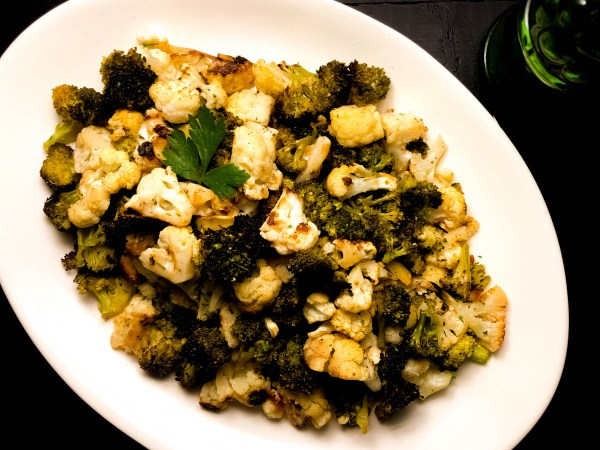 An oval serving plate of Skillet Roasted Broccoli and Cauliflower with a parsley garnish. | https://asprinklingofcayenne.com