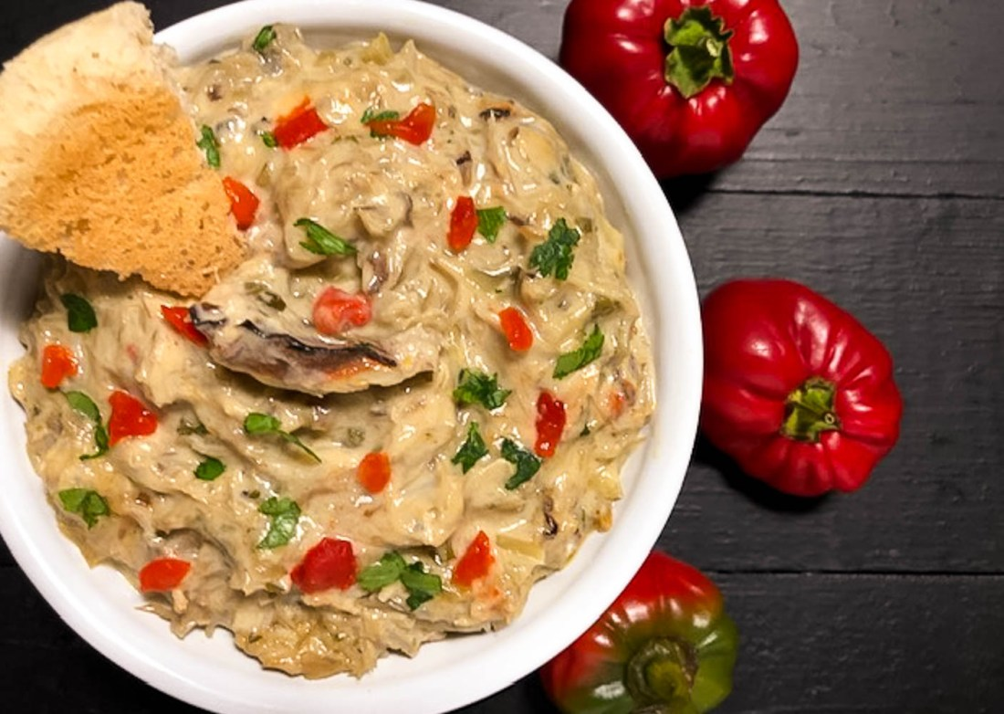 A round white bowl filled with Gluten Free Spicy Hot Crab and Artichoke Dip.