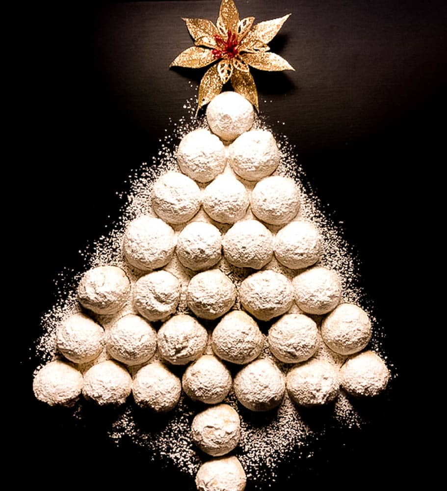 Gluten Free Pecan Balls Christmas Tree against a black background with a red and gold flower on top. | https://asprinklingofcayenne.com