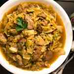 A round white bowl filled with Cajun Smothered Cabbage With Chicken and Sausage. | https://asprinklingofcayenne.com