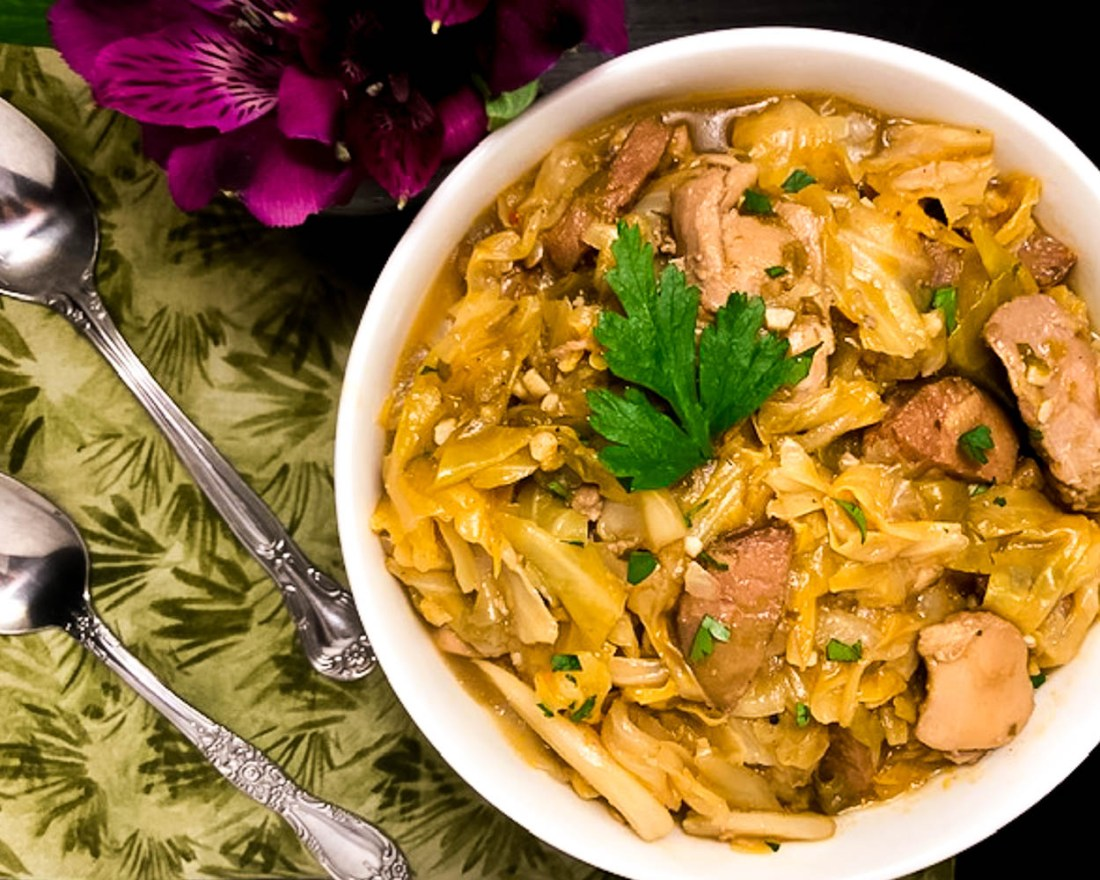 Two spoons, a green napkin, a base of magenta flowers and a small white bowl filled with Cajun Smothered Cabbage with Chicken and Sausage.