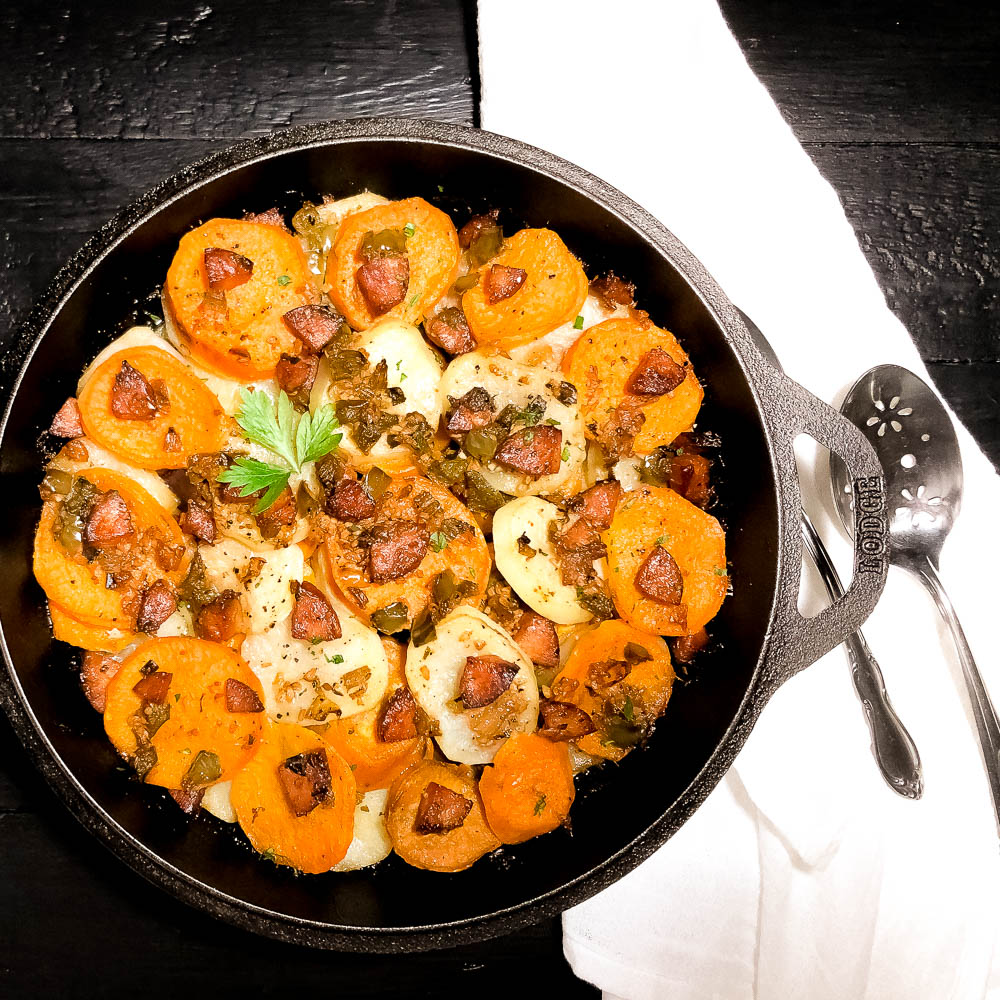 South Louisiana Sassified Skillet Potatoes with Sausage in a cast iron skillet with a white napkin and silver serving ware.