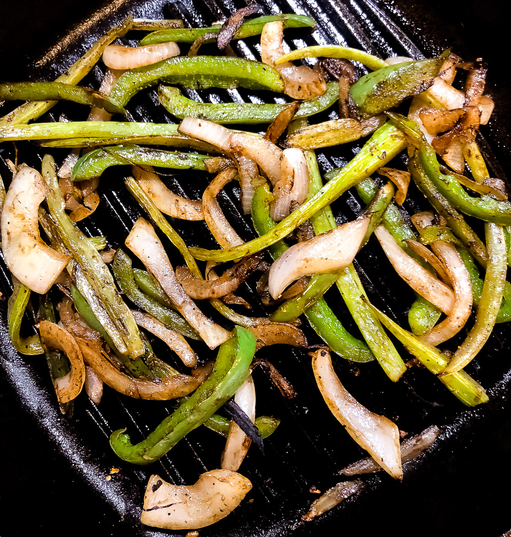 Browned Cajun trinity strips of onion, bell pepper and celery in a cast iron grill pan.