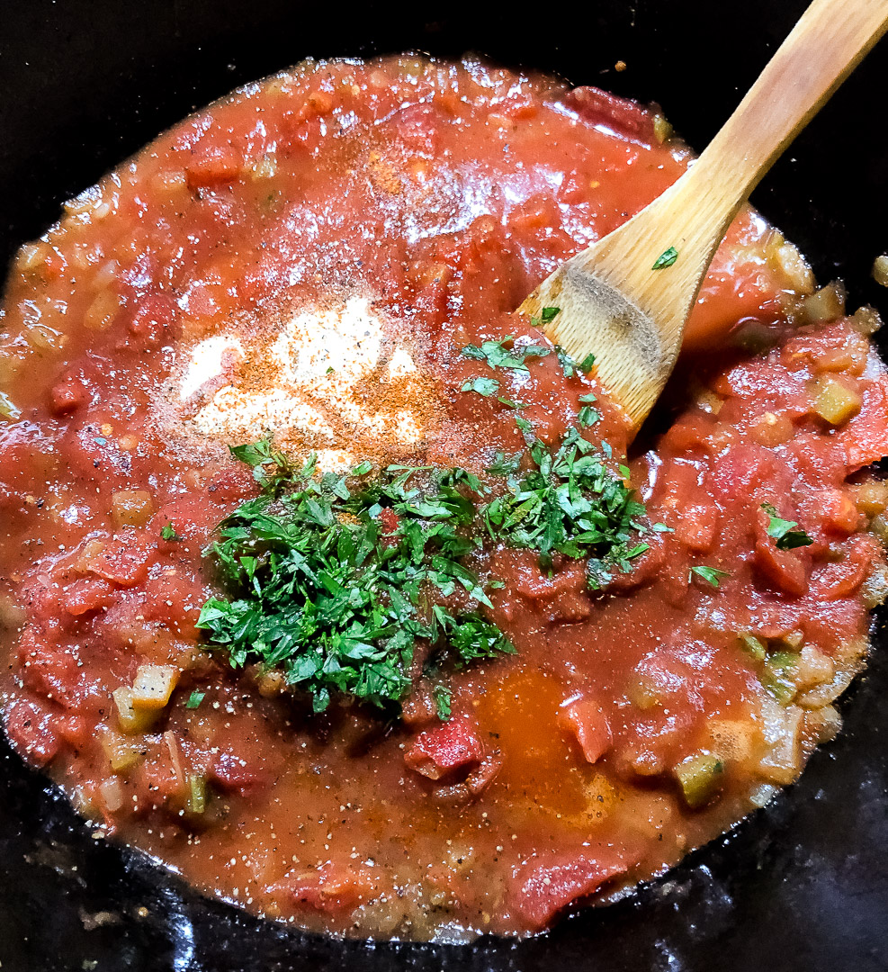 Creole red gravy ingredients in a black cast iron skillet.