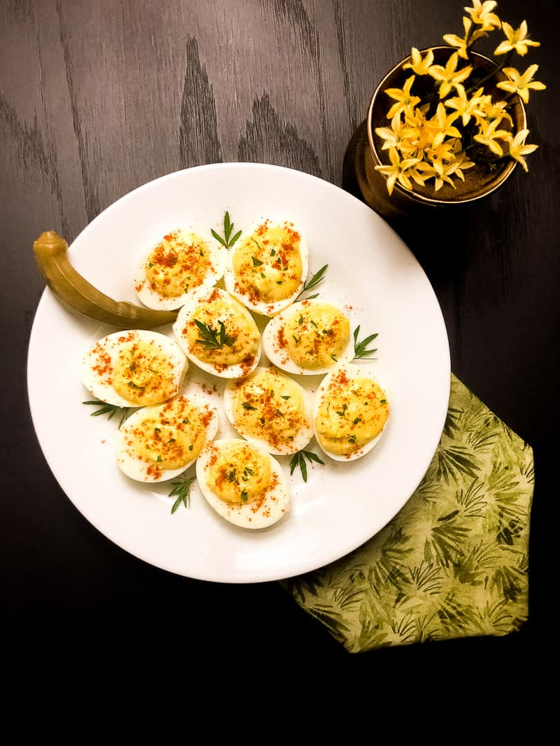 A white round plate filled with Cajun Deviled Eggs against a black background with a patterned green napkin and yellow flowers.