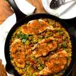A black cast iron skillet filled with Creole Baked Chicken with Rice and Okra