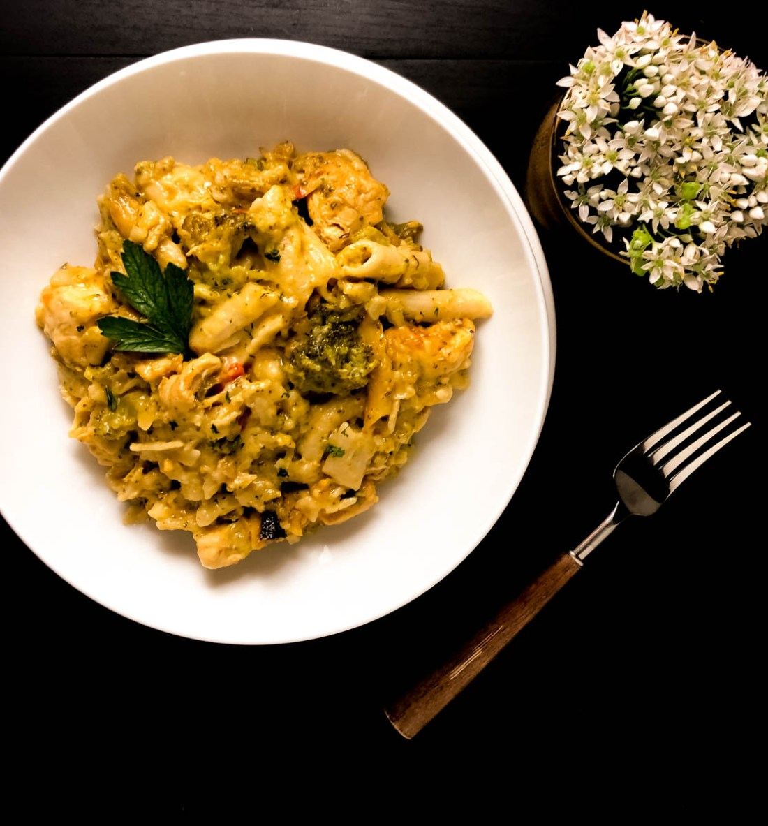 A round white plate filled with gluten free cheesy chicken broccoli pasta against a black background.