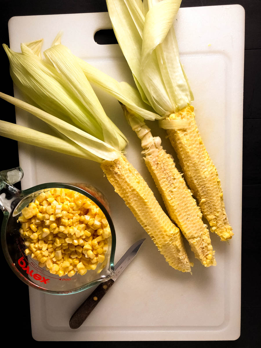 Three freshly peeled ears of corn on a cutting board with a knife.