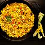 A round black cast iron skillet filled with spicy skillet corn maque choux against a black background with yellow flowers.