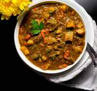 A white bowl filled with gluten free Cajun beef stew with yellow flowers against a black background.