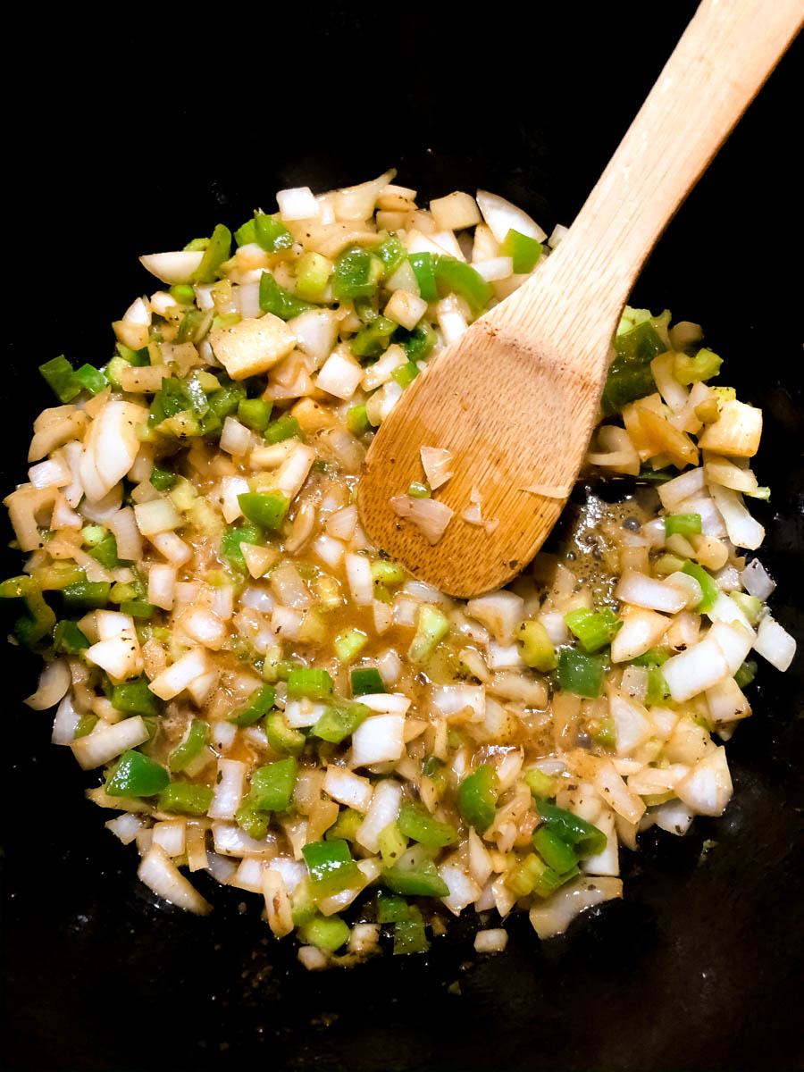 The Cajun trinity of onion, bell pepper and celery cooking down in a pot.