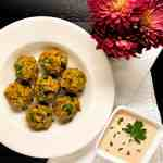 Cajun eggplant meatballs in a round white bowl with remoulade sauce and red flowers.