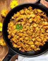 A black cast iron skillet filled with Cajun Style Gluten Free Stuffing