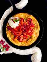 A black cast iron skillet filled with gluten free strawberry Dutch baby pancake against a black background.