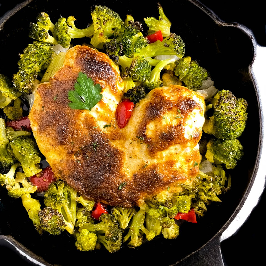 Square shot of Cajun Style Melt in Your Mouth Chicken with Broccoli in a black cast iron skillet.